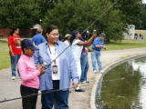 FWS employee helps child to fish