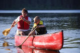 Man and boy paddle a canoe