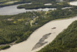 Aerial shot of river winding through forest and around village in Tetlin National Wildlife Refuge