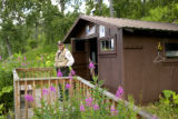 Service employee in front of Kodiak National Wildlife Refuge recreation cabin located at Uganik...