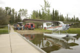 Seaplane docked while adults talk with U.S. Fish and Wildlife Service employee at Tetlin National...