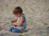 Young boy playing with his sand toys