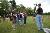 Service employee gives an archery demonstration to students