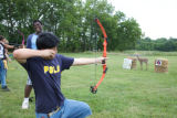 Young man learning bow and arrow skills
