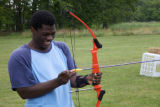 Youth is preparing to shoot a bow and arrow