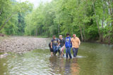 Educator and students look for macroinvertebrates