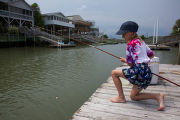 Girl lowering her fishing pole into the water