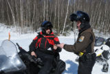 Service Law Enforcement Officer checks a sled driver