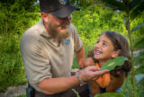 FWS employee shows young girl a Monarch caterpillar