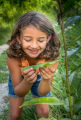 Young girl looking at Monarch caterpillar