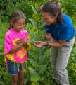FWS worker shows a young girl a Monarch caterpillar