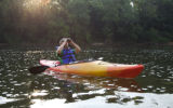 Man looking through binoculars while sitting in a kayak