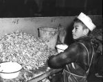 Native Alaskan boy working in fish house
