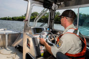 Fishery biologist pilots boat while collecting data on Asian carp