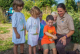 Group of children and fws employee looking at tagged monarch