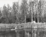 Man in canoe near tent camp