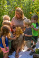 Children with fws employee look at monarch on stuffed bear