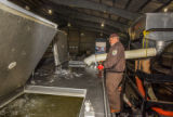 Service personnel prepare fish pump to load fish onto hatchery