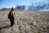 Firefighter looking out over burn field