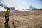 Firefighter stands beside sign