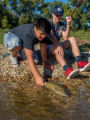 Two boys releasing small mouth bass