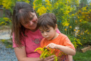 Mother and son with monarch butterfly on goldenrod flowers