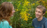 Mother and son looking at monarch butterfly on goldenrod
