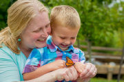 Woman and little boy looking at monarch butterfly on hand