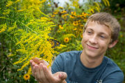 Teenage boy with monarch butterfly on goldenrod flowers