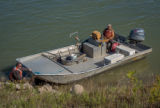 Biologists standing at boat on Missouri River