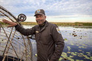 Employee leans on a docked airboat