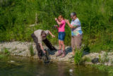 Older woman fishing with young redheaded girl, FWS employee netting trout