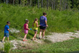 Family walks along stream with fishing rods