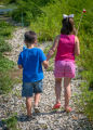 Little boy and girl going fishing, walking along creek