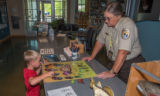 Visitor services specialist shows visiting child monarch butterfly poster