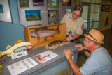 Visitor services specialist shows visitor fish and hellbender displays