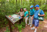 FWS Visitor services staffer shows interpretive panel to visitors