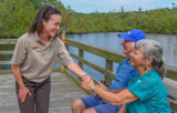 FWS Visitor services staffer greets visitors on boardwalk