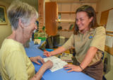 FWS Staffer greets visitor at visitor center desk