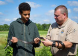 FWS Staffer shows young boy a Black Rat snake