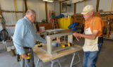 Volunteers work on wood project in shop