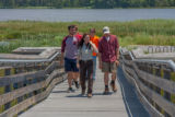 FWS staff leads group of high school students up boardwalk