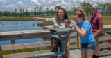 Girl takes cell phone picture of wetland with FWS employee pointing