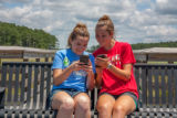 Students sittting on bench sharing cell phone pictures