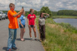 FWS staff with students taking cell phone pictures at wetland
