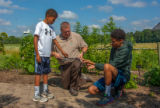 FWS staff with young boys handling black rat snake