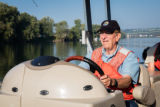 Volunteer, Richard Esker, drives a boat on the Ohio River