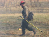 Firefighter with drip torch and hand tool