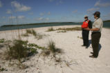 U.S. Fish and Wildlife Service employee speaking with visitor on beach